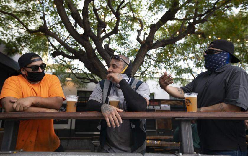 LOS ANGELES, CA - JUNE 30: Adan Gutierrez, left, Ramon Ayala, middle, and Vicente Fernandez, right, enjoy a beer outside the Central Market during the evening on Tuesday, June 30, 2020 in Los Angeles, CA. They were all wearing masks and keeping a distance for one another. Inside the brewery remains open because they also sell food. Citing the rapid pace of coronavirus spread in some parts of California, Gov. Gavin Newsom ordered seven counties including Los Angeles on Sunday to immediately close any bars and nightspots that are open and recommended eight other counties take action on their own to close those businesses. (Francine Orr / Los Angeles Times)