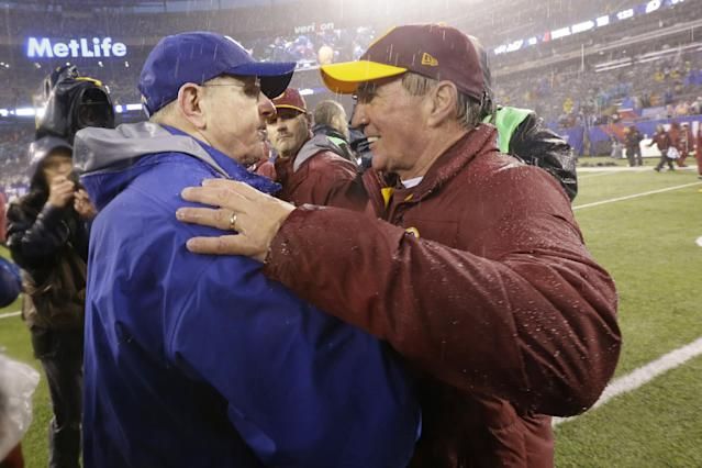 New York Giants head coach Tom Coughlin, left, and Washington Redskins head coach Mike Shanahan, right, meet after an NFL football game on Sunday, Dec. 29, 2013, in East Rutherford, N.J. The Giants won the game 20-6. (AP Photo/Julio Cortez)