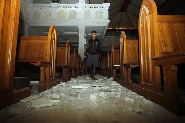 <p>A man walks inside a cathedral where debris has fallen after an earthquake in Bali, Indonesia, Sunday, Aug. 5, 2018. (Photo: Firdia Lisnawati/AP) </p>