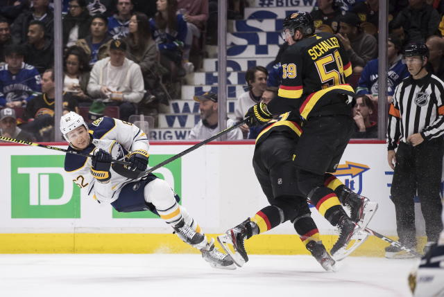 Buffalo Sabres' Brandon Montour, left, is tripped by Vancouver Canucks' Jay Beagle, back right, as Canucks' Tim Schaller (59) tries to avoid colliding with them during the second period of an NHL hockey game in Vancouver, British Columbia, Saturday, Dec. 7, 2019. (Darryl Dyck/The Canadian Press via AP)