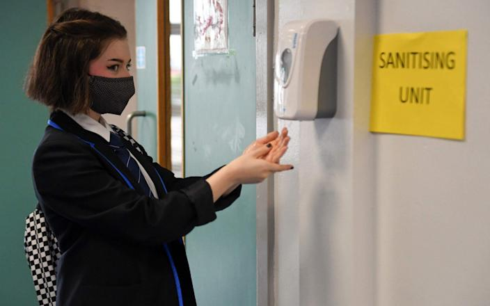 A secondary school pupil wearing a face mask sanitises her hands ahead of a lesson - Andy Buchanan/AFP