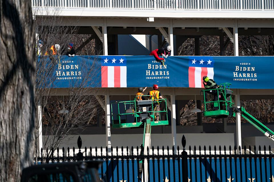 Workers hang banners featuring the names of Joe Biden and Kamala Harris before inauguration day.