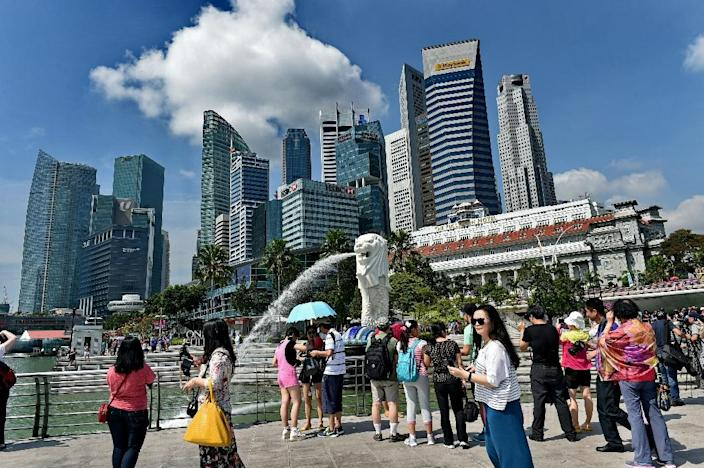 Tourists visit the famous Mer-lion while the business-district skyline looms against an azure sky on February 25, 2015, in Singapore, again ranked the globe's most business-friendly jurisdiction in a World Bank published October 27 (AFP Photo/Roslan Rahman)