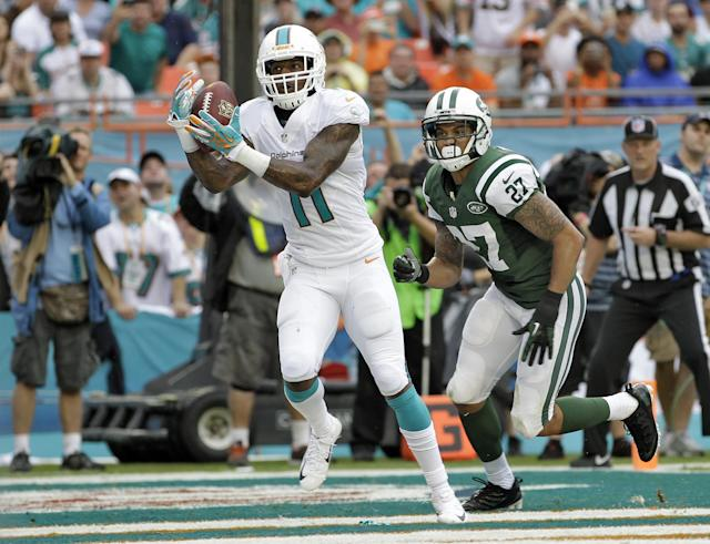 Miami Dolphins wide receiver Mike Wallace (11) pulls in a 5-yard touchdown pass in front of New York Jets cornerback Dee Milliner (27) during the second quarter of an NFL football game on Sunday, Dec. 29, 2013, in Miami Gardens, Fla. (AP Photo/Alan Diaz)