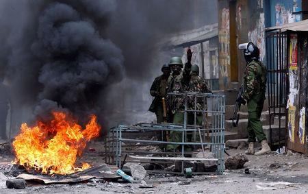 A policemen gestures during clashes with protesters, supporting opposition leader Raila Odinga, in Mathare, in Nairobi
