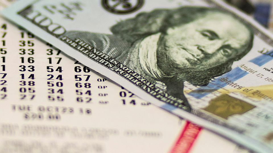 Picture shows a lottery ticket and a US 100 dollar. bill. A woman from Sydney was very close to winning half a million dollars in a. US lottery draw