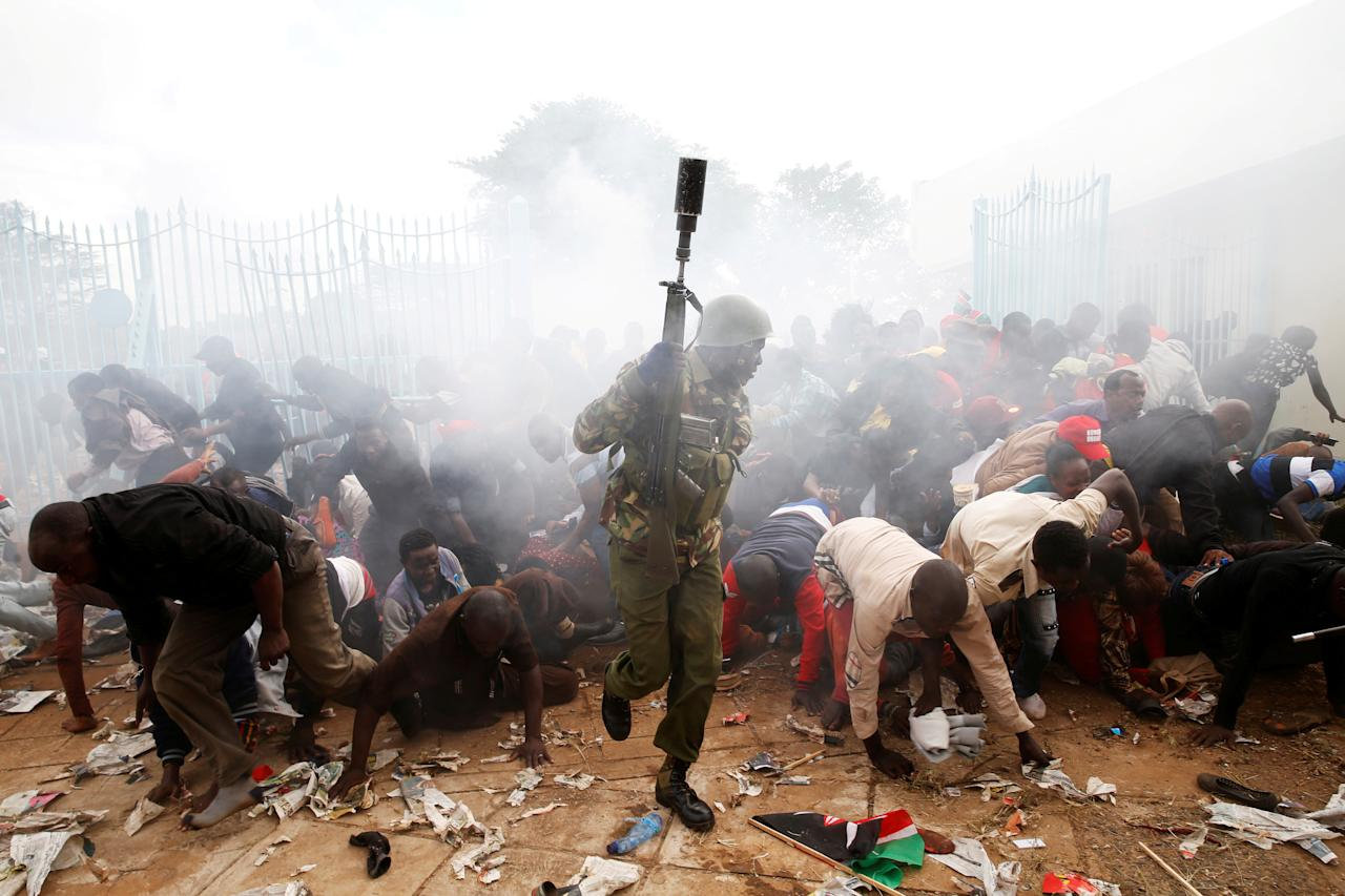 <p>People fall as police fire tear gas to try control a crowd trying to force their way into a stadium to attend the inauguration of President Uhuru Kenyatta at Kasarani Stadium in Nairobi, Kenya, Nov. 28, 2017. (Photo: Baz Ratner/Reuters) </p>