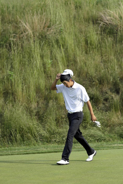 Michael Kim walks to his bunker shot near the 17th green during the third round of the U.S. Open golf tournament at Merion Golf Club, Saturday, June 15, 2013, in Ardmore, Pa. (AP Photo/Julio Cortez)