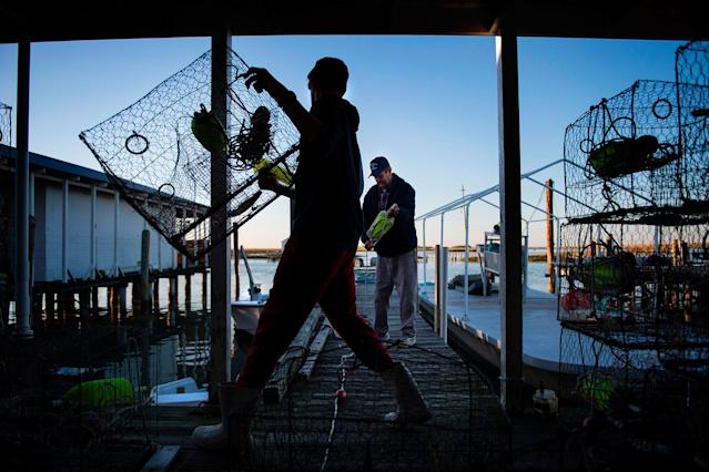 <p>Benjamin Eskridge (L) carries a crab trap as he helps his grandfather Allen Crocket (R) prepare for the next day of crabbing in Tangier, Virginia, May 15, 2017, where climate change and rising sea levels threaten the inhabitants of the slowly sinking island.<br> (Jim Watson/AFP/Getty Images) </p>