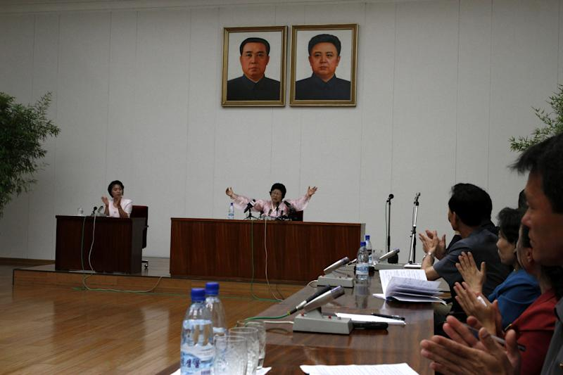 North Korean Pak Jong Suk sits under portraits of former North Korean leaders Kim Il Sung, left, and Kim Jong Il while speaking to reporters at the People's Palace of Culture in Pyongyang, North Korea, on Thursday, June 28, 2012. Pak told local and foreign reporters she was tricked into defecting to South Korea by agents who offered to arrange a reunion with her long-lost father, but returned home after being disillusioned with life in the South. Her account could not be verified by South Korean officials. (AP Photo/Kim Kwang Hyon)