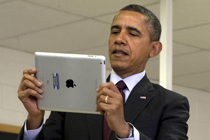 President Barack Obama looks at a classroom iPad in a seventh grade classroom before speaking about his ConnetED goal of connecting 99% of students to next generation broadband and wireless technology within five years, Tuesday, Feb. 4, 2014, at Buck Lodge Middle School in Adelphi, Md. (AP Photo/Jacquelyn Martin)