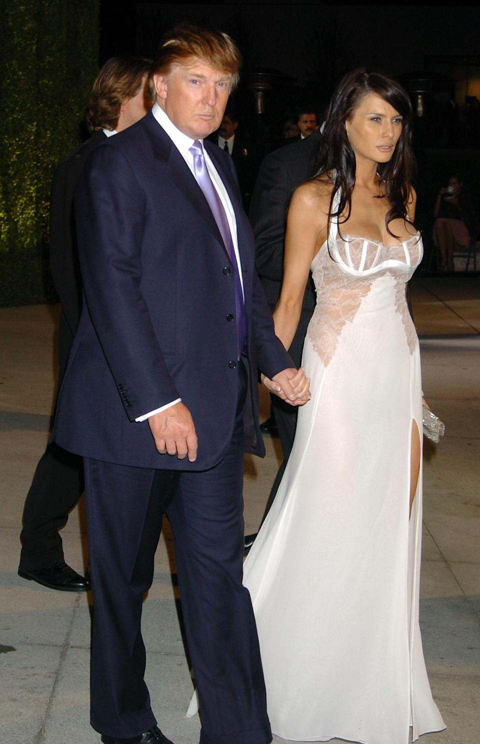 <p>At the 2004 Oscars, Melania wore a lacy lingerie-style white bustier dress with a thigh-high slit. The sexy look was pulled together by her dark shoulder-length locks. Donald went with a navy suit, white dress shirt, and lilac tie. (Photo: Getty Images) </p>