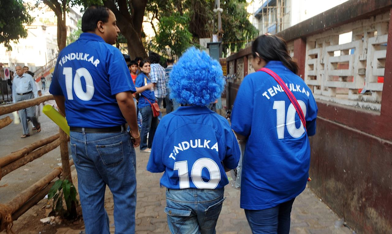 An Indian family wearing t-shirts of Mumbai Indians cricketer Sachin Tendulkar makes their way towards the venue of the  IPL Twenty20 cricket match between Mumbai Indians and Royal Challengers Bangalore at The Wankhede Stadium in Mumbai on May 9, 2012.  RESTRICTED TO EDITORIAL USE. MOBILE USE WITHIN NEWS PACKAGE    AFP PHOTO/Indranil MUKHERJEE        (Photo credit should read INDRANIL MUKHERJEE/AFP/GettyImages)