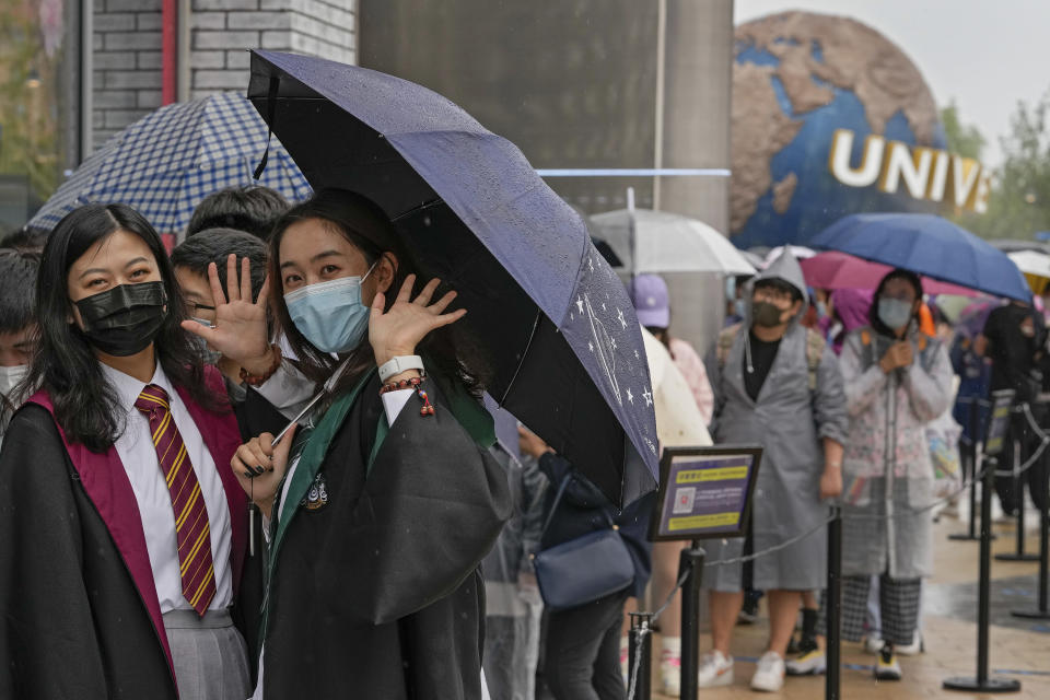 Women wearing face masks to help protect themselves from coronavirus wave as they line-up to enter a merchandise store at the Universal Studios Beijing in Beijing, Monday, Sept. 20, 2021. Thousands of people brave the rain visit to the newest location of the global brand of theme parks which officially opens on Monday. (AP Photo/Andy Wong)