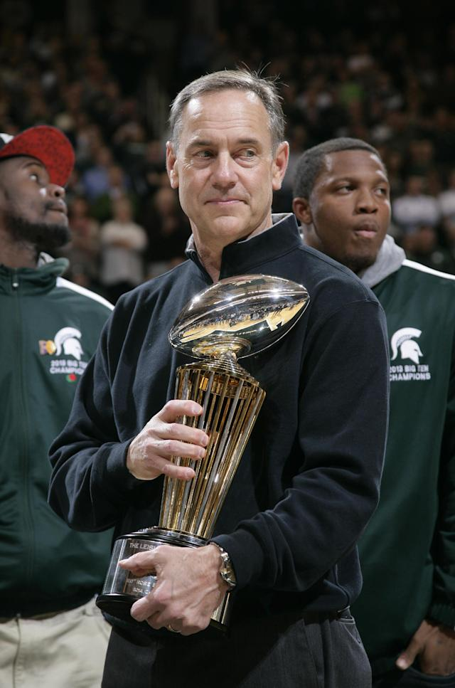 Michigan State football coach Mark Dantonio holds the 100th Rose Bowl championship trophy at an NCAA college basketball game between Michigan State and Ohio State, Tuesday, Jan. 7, 2014, in East Lansing, Mich. (AP Photo/Al Goldis)