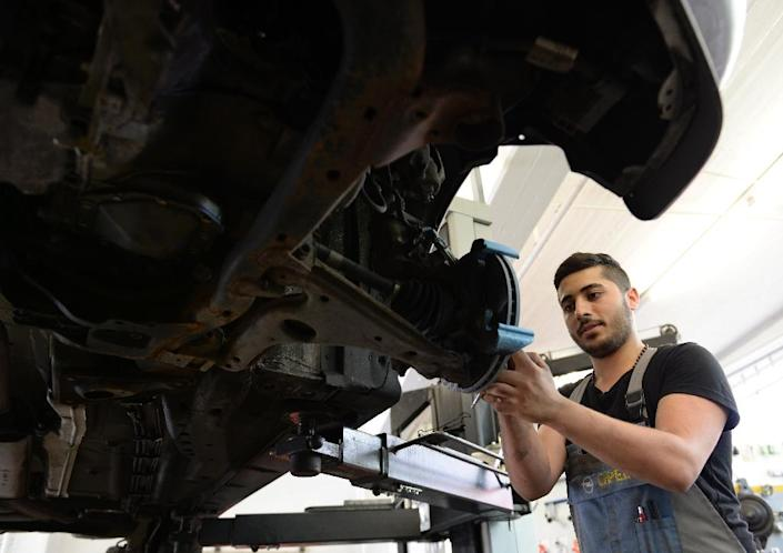 Syrian refugee George Romanos works on a car at a workshop in Bobingen, southern Germany, on July 14, 2015 (AFP Photo/Christof Stache)