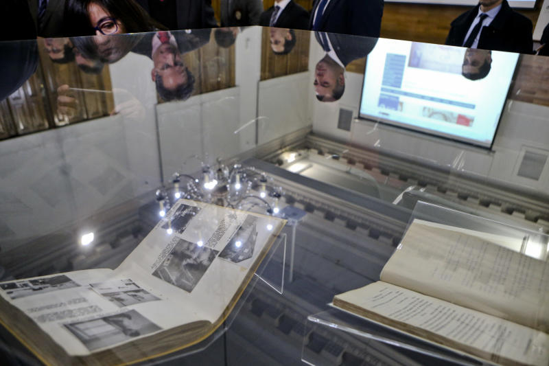 People look at declassified World War II archives presented by Chile's Investigative Police, that unveil Nazi activity in Chile that sought to sabotage Chilean factories and destroy the Panama Canal, at a National Library in Santiago, Chile, Thursday, June 22, 2017. The Police handed the files, four books that cover the period 1937-1944, over to the National Archive. (AP Photo/Esteban Felix)
