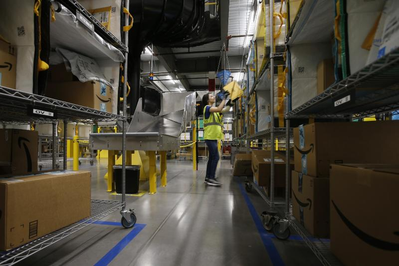In this Dec. 17, 2019, photo Jocelyn Nieto stows packages into special containers after Amazon robots deliver separated packages by zip code at an Amazon warehouse facility in Goodyear, Ariz. Doing your job side-by-side with robots isn't easy. According to their makers, the machines should take on the most mundane and physically strenuous tasks. In reality, they're also creating new forms of stress and strain in the form of injuries and just the unease of working in close quarters with mobile half-ton devices that direct themselves. (AP Photo/Ross D. Franklin)