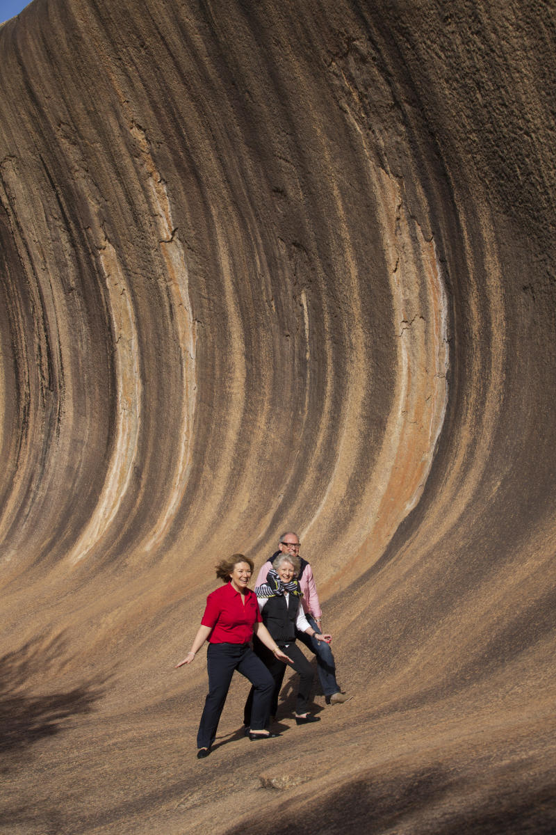 Three travellers pose at Wave Rock in Margaret River, Western Australia.