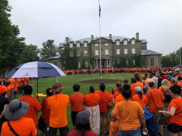 Hundreds can be seen here at the Government House on Woodstock Road at the end of a healing walk to mark Resilience Day, planned by the Wolastoqey Nation in place of Canada Day. (Gary Moore/CBC - image credit)
