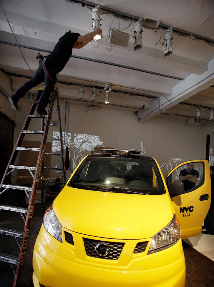 A technician adjusts lighting above the prototype of a Nissan NV 200 New York City taxi, in New York, Monday, April 2, 2012. The iconic New York City taxi has gotten a passenger-friendly makeover from Nissan with low-annoyance horns, USB chargers and germ-fighting seats to cut down on bad odors. Medallion owners will be required to buy the Nissan NV 200 at a cost of about $29,000 starting in late 2013. (AP Photo/Richard Drew)