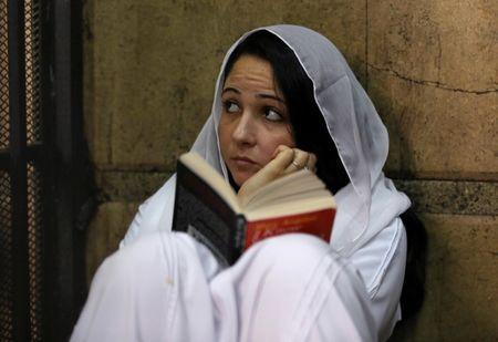 Aya Hijazi, founder of a non-governmental organisation that looks after street children, sits reading a book inside a holding cell at a court in Cairo