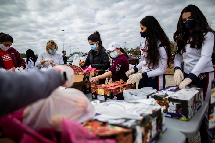 Texans Cheerleaders and other volunteers pack food to distribute to hundreds of people picking up supplies from their cars after frigid temperatures left the Houston area depleted of resources, Sunday, Feb. 21, 2021, in Houston.