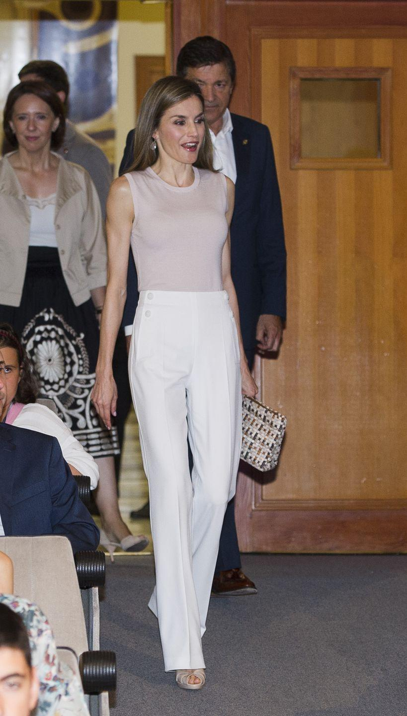 <p>She's frequently seen in light, streamlined neutrals, like this pink shell and white-pants combo from Boss. </p>