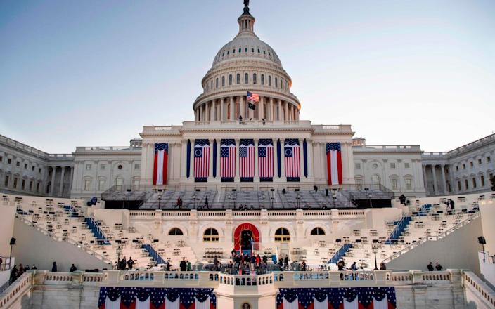 The sun rises behind the US Capitol as preparations are made prior to the 59th inaugural ceremony for President-elect Joe Biden and Vice President-elect Kamala Harris - CAROLINE BREHMAN/AFP