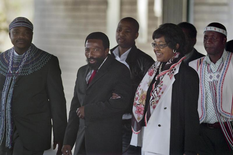 King Buyelekhaya Zwelibanzi Dalindyebo, center-left, the Xhosa king who rules the Thembu tribe to which the Mandela family belongs, escorts Nelson Mandela's former wife Winnie Madikizela-Mandela to her car, after they visited the Mediclinic Heart Hospital where former South African President Nelson Mandela is being treated in Pretoria, South Africa Tuesday, July 9, 2013. No official update was made Tuesday morning on the status of the ailing 94-year-old, who was admitted June 8 to the hospital for a recurring lung infection, though court documents say he is breathing with the help of a respirator. (AP Photo/Ben Curtis)