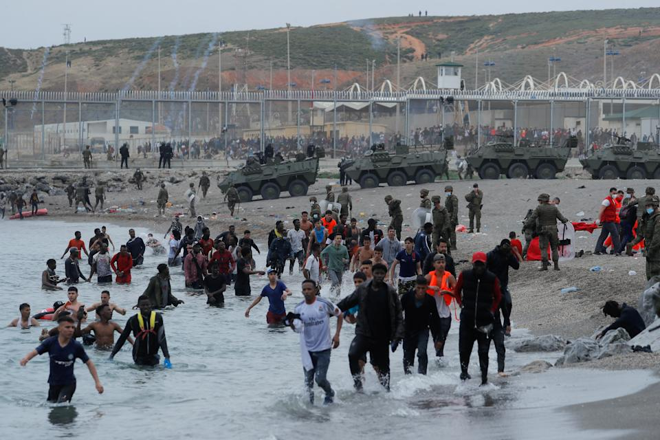 Moroccan citizens walk in the water as Spanish legionnaires patrol the area near the fence on a beach in El Tarajal. (Reuters)
