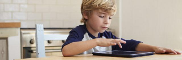 Young boy using tablet computer at kitchen table.