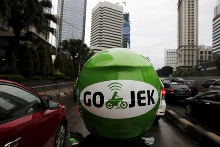 FILE PHOTO: A Gojek driver rides his motorcycle through a business district street in Jakarta,Indonesia, June 9, 2015. REUTERS/Beawiharta/File Photo