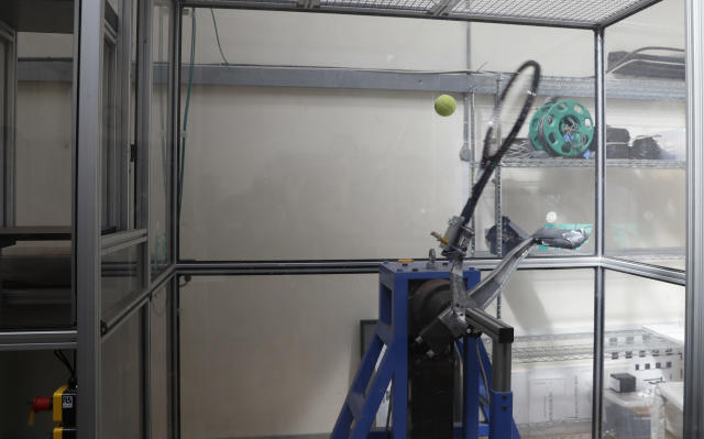 "In this photo taken Friday June, 28, 2019, a serve-simulating robot arm nicknamed ""Myo,"" from the Greek word for ""muscle"" is about to hit a ball dropped from above at the International Tennis Federation (ITF) lab in Roehampton, near Wimbledon south west London. Based for about 20 years in a three-room area on what used to be a pair of squash courts in Roehampton, the ITF tech lab is filled with more than $1 million worth of machines that help make sure rules are followed and parameters are met. (AP Photo/Alastair Grant)"