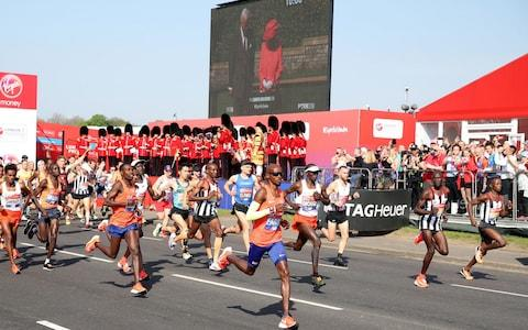 Sir Mo Farah makes his way past the video screen of Queen Elizabeth II - Credit: Adam Davy/PA Wire