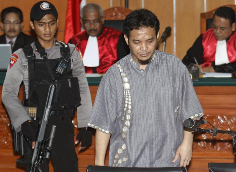 Ali Imron, right, sentenced life imprisonment for the 2002 Bali bombings, escorted by a police officer, arrives for a trial of Umar Patek, an Indonesian militant charged in the terrorist attacks, at West Jakarta District Court in Jakarta Thursday, March 22, 2012. Patek faces a maximum penalty of death by firing squad if convicted of various terror-related and criminal charges, most of which are tied to the Bali bombings that left 202 people dead. (AP Photo/Tatan Syuflana)