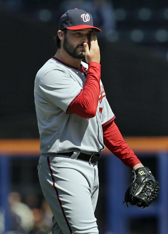 Washington Nationals pitcher Tanner Roark wipes his face during the first inning of the baseball game against the New York Mets at Citi Field, Thursday, April 3, 2014, in New York. (AP Photo/Seth Wenig)