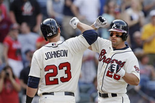 Atlanta Braves ' Dan Uggla, right, celebrates with teammate Chris Johnson (23) after hitting a solo home run in the eighth inning of a baseball game against the Chicago Cubs in Atlanta, Sunday, April 7, 2013. Atlanta won 5-1. (AP Photo/John Bazemore)