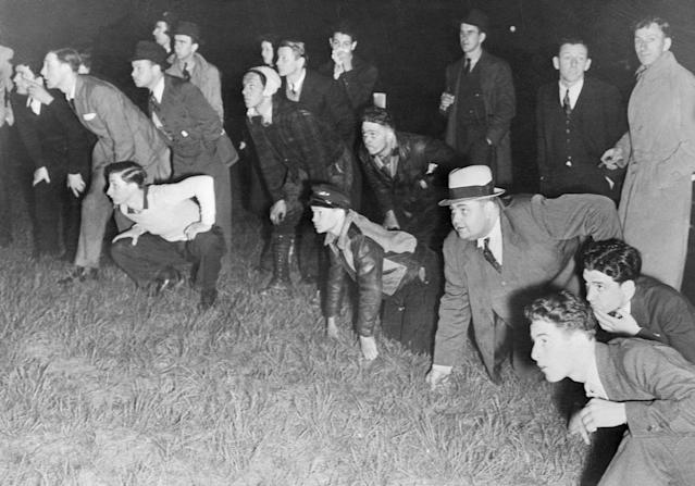 <p>Crouching low on the ground, these spectators who had gathered at Lakehurst, N.J., to watch the German dirigible Hindenburg land on its first flight of the year, saw the craft burst into flames, burning over 30 of its passengers and crew to death on May 6, 1937. (Bettman via Getty Images) </p>