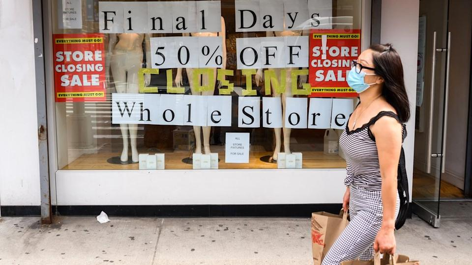 A person walks by a going out of business sign displayed outside a retail store in New York City
