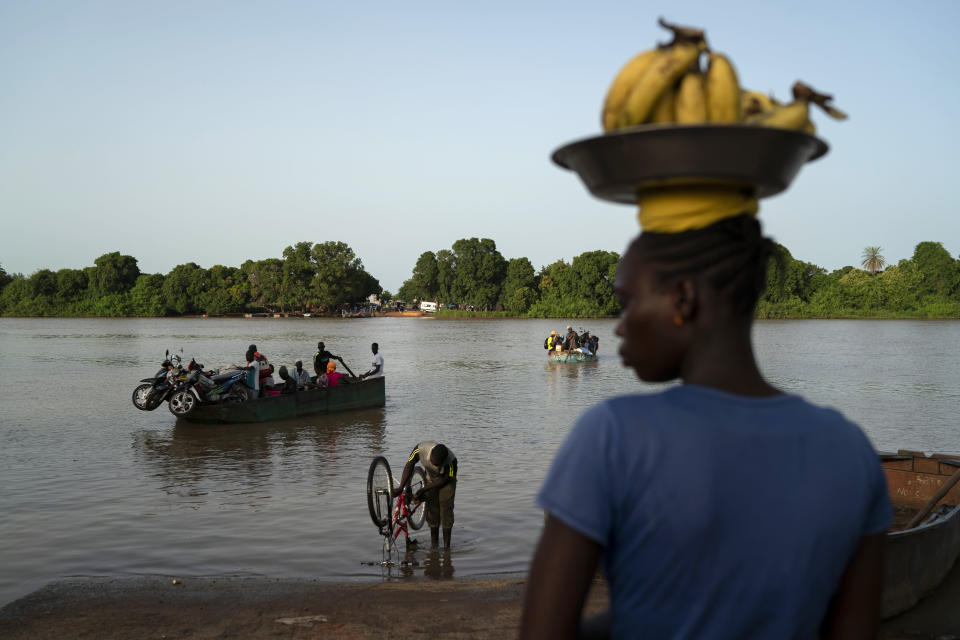 Carrying bananas for sale, a woman waits for the boat to cross the Gambia river in Bansang, Gambia, Tuesday, Sept. 28, 2021. As health officials in Gambia and across Africa urge women to be vaccinated, they've confronted hesitancy among those of childbearing age. Although data on gender breakdown of vaccine distribution are lacking globally, experts see a growing number of women in Africa's poorest countries consistently missing out on vaccines. (AP Photo/Leo Correa)