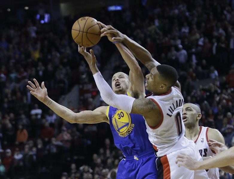 Golden State Warriors guard Stephen Curry, left, battles for a rebound with Portland Trail Blazers guard Damian Lillard off a missed free throw by Portland Trail Blazers forward Nicolas Batum, from France, at right, in the final seconds of an NBA basketball game in Portland, Ore., Sunday, March 16, 2014. Curry led the Warriors with 37 points, six of them three point shots, to beat the Trail Blazers 113-112. (AP Photo/Don Ryan)