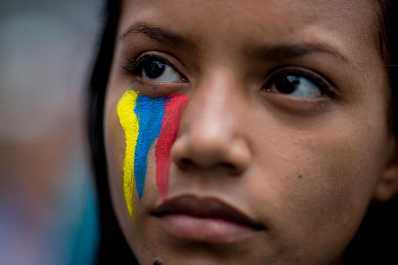 A demonstrator wearing painted stripes that represent Venezuela's national flag attends a rally with humans rights activist in Caracas, Venezuela, Friday, Feb. 28, 2014. The start of a weeklong string of holidays leading up to the March 5 anniversary of former President Hugo Chavez's death has not completely pulled demonstrators from the streets as the government apparently hoped. President Nicolas Maduro announced this week that he was adding Thursday and Friday to the already scheduled long Carnival weekend that includes Monday and Tuesday off, and many people interpreted it as an attempt to calm tensions. (AP Photo/Rodrigo Abd)
