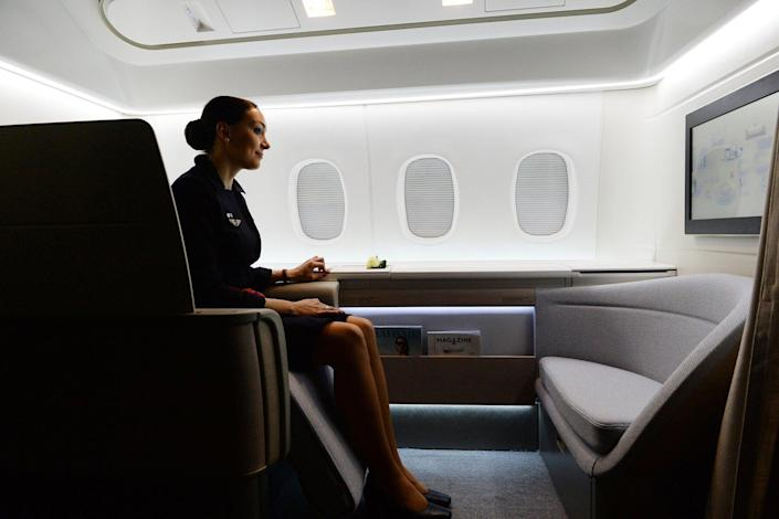 """An Air France attendant shows off the airline's """"haute couture"""" suite featuring a seat that reclines into a bed stretching 2.01 metres long and 77 centimetres across (6 ft 7 ins and 30 inches) -- one of the most spacious in the world, in Shanghai on May 7, 2014"""