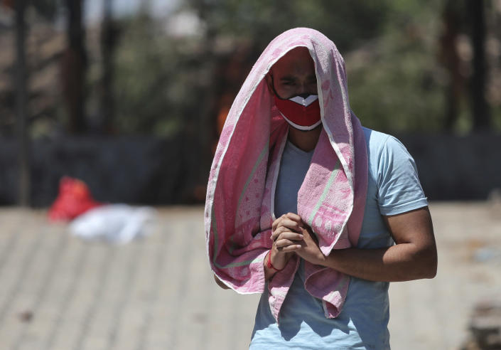 A relative of a person who died of COVID-19 reacts during cremation in Jammu, India, Monday, May 24, 2021. India crossed another grim milestone Monday of more than 300,000 people lost to the coronavirus as a devastating surge of infections appeared to be easing in big cities but was swamping the poorer countryside. (AP Photo/Channi Anand)