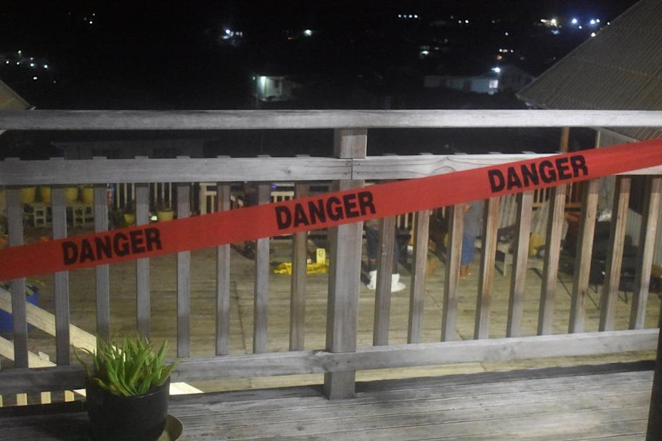 A photo of the scene with tape that reads 'DANGER' strapped to a balcony railing.