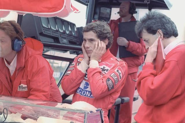 Senna, centre, shields his ears from the engine noise during a testing session at Silverstone (PA)