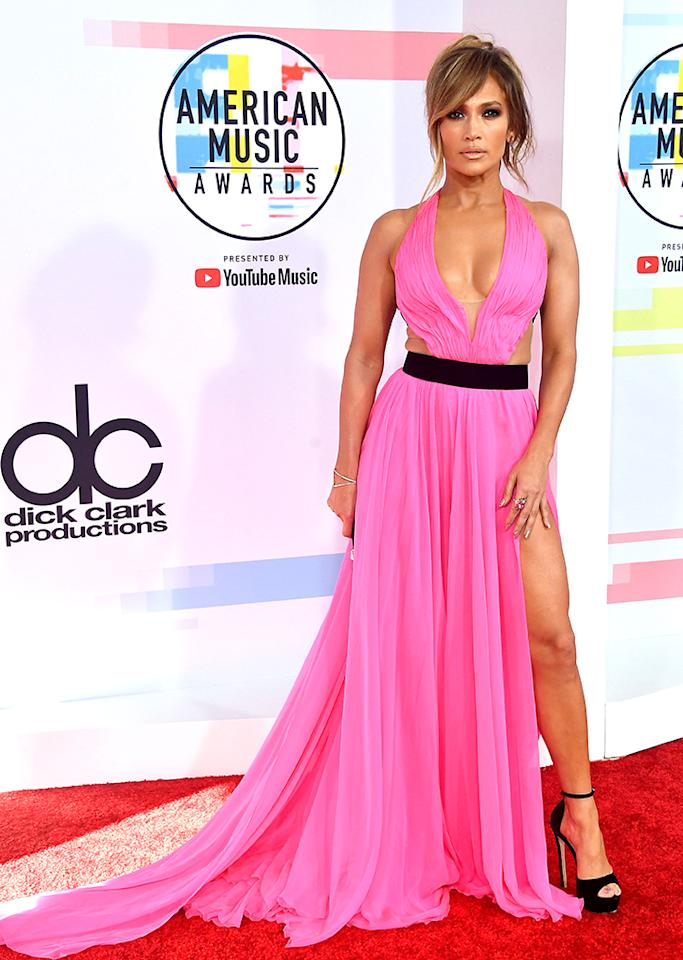 <p>All hail Jennifer Lopez, who stood out in a hot pink gown with cutouts — and a cape! — designed by Georges Chakra Couture. The entire look was very J.Lo. (Photo: Frazer Harrison/Getty Images) </p>