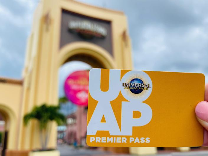 hand holding universal annual pass card in front of theme park entrance