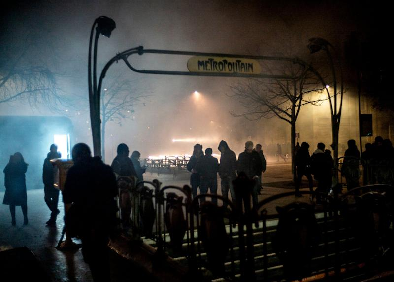 People stand next to the entrance of a metro station at the end of a demonstration in Paris (AP)